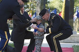 Sam Brownback - Brownback and 1st Infantry Division Commanding General present a medallion to a child whose father died serving in Iraq.