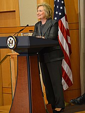 Clinton standing behind lectern wearing a charcoal-colored suit, smiling and looking to her right