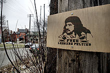 "A sign nailed to a tree shows the image of a man and reads ""Free Leonard Peltier."