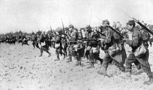 A line of men in the sand with bayonets.