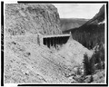 General view of viaduct showing approach road retaining wall at left. - Golden Gate Viaduct, Lake, Teton County, WY HAER WYO,20-YELNAP,2-4.tif