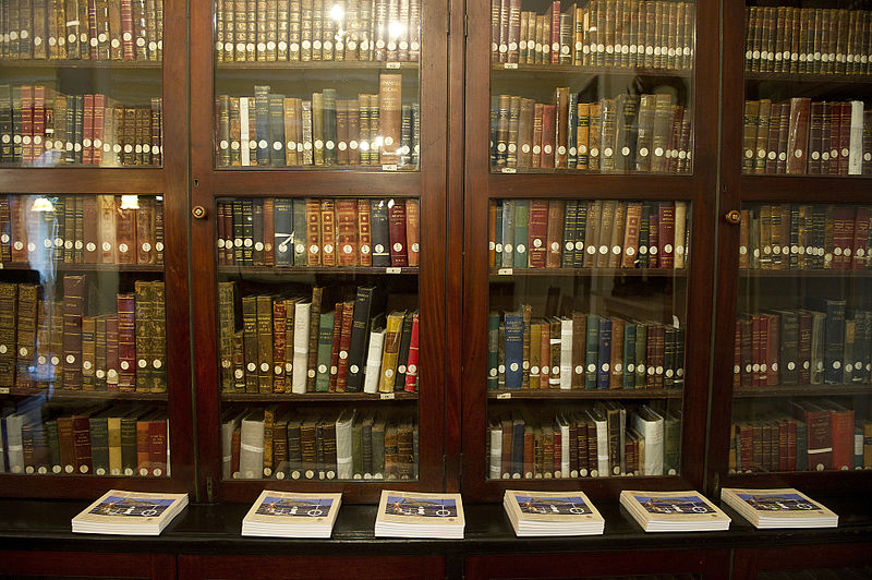 Books on wooden bookshelves with glass doors