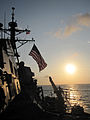 Guided missile destroyer USS Mustin (DDG 89) steams into formation as the sun rises over the Philippine Sea Jan. 29, 2012 120129-N-RM161-001.jpg