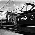 HUA-151717-Afbeelding van een electrische locomotief uit de serie 1100 langs een perron van het N.S.-station Amsterdam C.S. te Amsterdam. Op de achtergrond staat een electrische locomotief uit de serie 1200 met .jpg