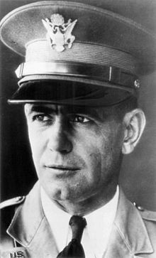 Facial shot of a cleancut middleaged uniformed man in dress hat with face turned quartering toward left side of shot