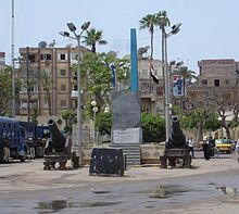 """Photo of a public square in Rashid (Rosetta) in Egypt featuring a replica of the Rosetta Stone"""