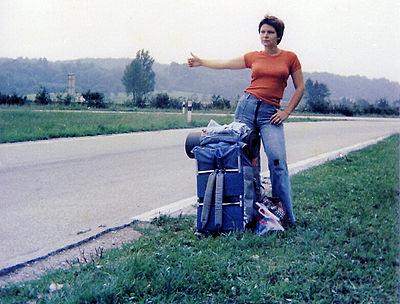 Esta viajante à boleia no Luxemburgo em 1977 ilustra gesto universal de pedir boleia: na berma da estrada, em pé, de polegar estendido.