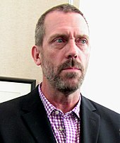 A Caucasian man with a beard, standing, while wearing a formal jacket and light, plaid shirt.