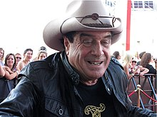 Upper body shot of a smiling man in a cowboy hat and black leather jacket. He is wearing a black T-shirt with a gold design which is mostly out of shot. In the background are people behind a barrier fence.