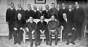 The Inquiry - 1919 group photo of Inquiry members at the Paris Peace Conference, sitting left to right: Charles Homer Haskins, Western Europe; Isaiah Bowman, Chief of Territorial Intelligence; Sidney Edward Mezes, Director; James Brown Scott, International Law; David Hunter Miller, International Law; standing Charles Seymour, Austria-Hungary; R. H. Lord, Poland; William Linn Westermann, Western Asia; Mark Jefferson, Cartography; Edward Mandell House; George Louis Beer, Colonies; D.W. Johnson, geography; Clive Day, Balkans; W. E. Lunt, Italy; James T. Shotwell, History; Allyn Abbott Young, Economics