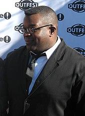 Мужчина в костюме, в очках и смотрит налево