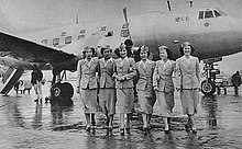 A black and white photograph of a Martin 2-0-2 aircraft with six cabin crew standing in front of the aircraft