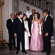 Mrs. Kennedy, the president, André Malraux, Marie-Madeleine Lioux Malraux, Lyndon B. Johnson and Lady Bird Johnson having just descended the White House Grand Staircase on their way to a dinner with the French cultural minister, May 1962. Mrs. Kennedy wears a gown designed by Guy Douvier for Christian Dior.