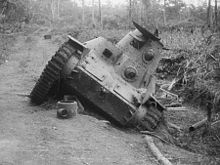 A small tank on a road, which is at a 45 degree angle due to one side being in the ditch beside the road