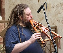 Lanier blowing into a woodwind instrument with several chambers