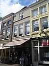foto van Pand met gepleisterde lijstgevel en jongere winkelpui