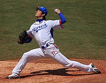 "A man in a white baseball jersey with ""KOREA"" on the chest in blue and ""17"" on his leg in orange pitches a baseball from the pitcher's mound with his left hand. He is wearing a black baseball glove on his right hand."