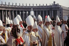 Many bishops robed in while stand in the sunshine in St Peter's Square. Most wear white pointed mitres on their heads, except a black bishop in the foreground who wears a distinctive embroidered velvet hat. Most of the men are elderly, and some have long white beards.