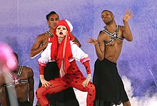 Gaga in a red bodysuit and hood, dancing at the center flanked by her dancers.