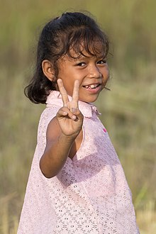 Little girl giving V-sign in the sunshine in Laos.jpg