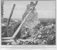 Monochrome image on newsprint type paper. Destroyed house with one remaining wall and visible roof timbers. Image of soldier dressed in British helmet and great-coat and rifle lying prone, peering over rubble towards the top right of picture.