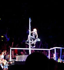 Faraway image of a stage and a woman hunched on a carousel horse which is attached around a pole. The woman wears a tight black dress with her hair in knots. Near the ground a long line of rods are visible, behind which the audience member are seen.