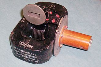 Cavity magnetron - Obsolete 9 GHz magnetron tube and magnets from a Soviet aircraft radar.  The tube is embraced between the poles of two horseshoe-shaped alnico magnets (top, bottom), which create a magnetic field along the axis of the tube. The microwaves are emitted from the waveguide aperture (top) which in use is attached to a waveguide conducting the microwaves to the radar antenna. Modern tubes use rare earth magnets which are much less bulky.
