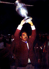 Photo of a man with a moustache, wearing a suit, triumphantly raising a trophy