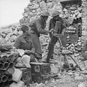 Men of the 6th Battalion, Royal West Kent Regiment man a 3-inch mortar on Monastery Hill, Cassino, Italy, 26 March 1944. NA13365