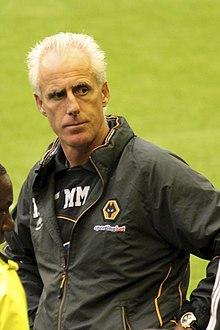 A man wearing a black waterproof jacket, with the Wolverhampton Wanderers logo on the left side.