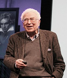 Half-length portrait of a white-haired man in his seventies talking. A painting of Beethoven is in the background.