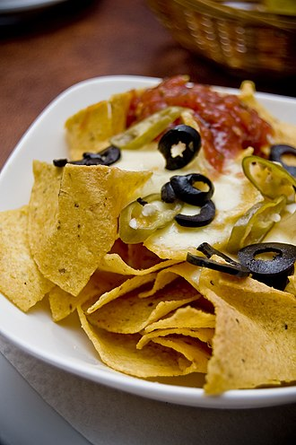 Nachos - Nachos with tortilla chips, melted cheese, olives, jalapeño peppers, sour cream, and salsa