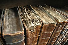 Colour photograph of the top of old books on a shelf, with frayed edges, warped pages and similar signs of age.