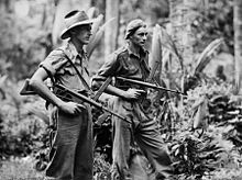 Two men wearing military style uniforms, one wearing a slouch hat, the other a general service cap, carrying weapons in a jungle setting
