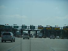 Multi-lane toll plaza before bridge: half cash and half E-ZPass lanes