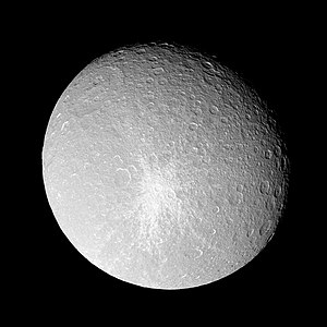 A spherical body is almost fully illuminated. Its grayish surface is covered by numerous circular craters. The terminator is located near the upper-right limb. A large crater can be seen near the limb in the upper-left part of the body. Another smaller bright crater can be seen in the center. It is surrounded by a large bright patch having the shape of a five-pointed star.