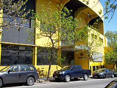 Yellow, multi-story building with cars parked in front
