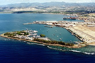 Rafael Cordero Santiago Port of the Americas - This 1999 photograph of the Port of Ponce and its surrounding lands was taken before the proposed expansion. In the foreground are the Club Náutico de Ponce and La Guancha Boardwalk. At the background is barrio Playa de Ponce. Further in the background are barrio Canas and the hills of western Ponce.