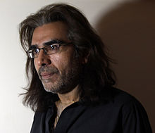 An image in semi-profile of an adult man with shoulder-length black hair, closely trimmed facial hair and glasses.