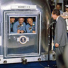 "The three crew members smiling at the President through the glass window of their metal quarantine chamber. Below the window is the Presidential Seal, and above it is stenciled on a wooden board ""HORNET + 3"". President Nixon is standing at a microphone, also smiling. He has dark crinkly hair and a light gray suit."