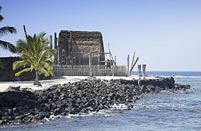 thatched structure with carvings at sea shore