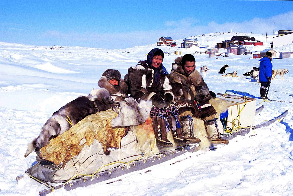 Color photograph of three Inuit persons on a traditional qamutik (sled), in a snow-covered landscape in Cape Dorset.