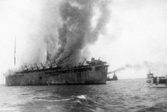 RMS Empress of Asia - The Empress of Asia on fire and gradually sinking after being attacked by Japanese dive-bomber aircraft en-route from India to Singapore. To the extreme-right of the photograph, the Sultan Shoal Lighthouse can be seen.