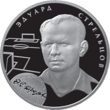 A silver coin with Strelstov's head and neck illustrated in relief upon it, accompanied by the outlines of a football pitch and a football and his name in Russian.