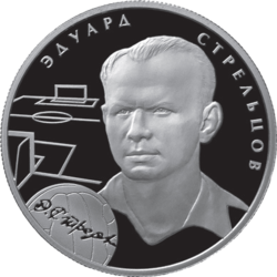 A silver coin, with a man's head and neck illustrated in relief upon it, accompanied by the outlines of a football pitch and a football. Upon the football is a facsimile of an autograph, and around the man's head is his name written in his native language, Russian.