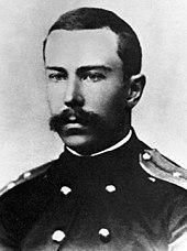 Un hombre joven con un bigote completo pero cuidadosamente recortado, vestido con un uniforme naval oscuro
