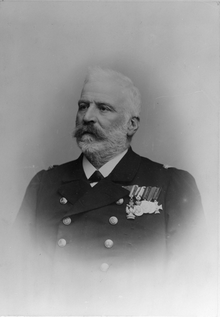 A black-and-white photo of an elderly naval officer in full dress uniform, with several medals pinned to his left breast.