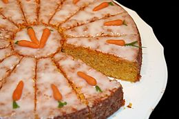 A round cake covered with icing sugar and marzipan carrot.