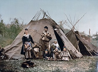 Goahti - A Sami family in front of goahti.  The tent in the background is a lavvu.  Note the differences in the pole placement of the two structures.  This photo was taken around 1900 in northern Scandinavia.