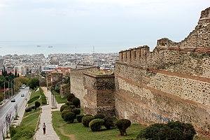 Foto di un muro medievale in pietra con torri, con una città moderna e il mare sullo sfondo